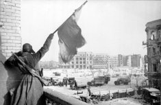Soviet soldier waving the Red Banner over the central plaza of Stalingrad in 1943.