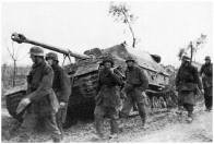 Soldats of the Hermann Goering division pass a destroyed elephant tank destroyer.