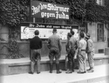 "A group of men read a propaganda billboard titled ""The Jews Are Our Misfortune"", 1933."