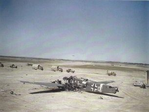 A convoy of RAF vehicles passing a crashed Junkers Ju 52 transport aircraft which was destroyed on the Gabes airfield when it was captured at the end of March 1943.
