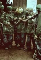Colorized image of Fallschirmjäger examine a captured Thompson sub-machine gun.