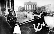 After the battle, Soviet soldiers hoist the Soviet flag on the balcony of the Hotel Adlon in Berlin.