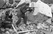 "Henryk Ożarek ""Henio"" (left) and Tadeusz Przybyszewski ""Roma"" (right) from ""Anna"" Company of ""Gustaw"" Battalion in the region of Kredytowa-Królewska Street. ""Henio"" holds a Vis pistol and ""Roma"" fires a Błyskawica submachine gun. October 3, 1944."