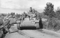 Panzer Mk IIIs in Tunisia move onto a roadway.