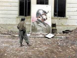 An American soldier looks at a bullet-riddled portrait of the Italian Dictator Benito Mussolini (1883 – 1945) which was taken from the former Fascists political headquarters in Anzio, Italy. February 7,1944.