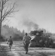 An American patrol moves toward a smoldering German tank, with its crew still inside, Belgium, December 1944.