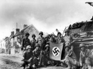American infantrymen, left behind to mop up last stronghold of Nazis in Falaise Gap area of northwestern France, line up in front of wrecked German tank with a captured swastika flag, 1944.