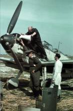 """Messerschmitt Bf 109 """"White 13"""" with its engine cowling removed. A bullet hole is visible in the machine-gun cover sitting on the ground, indicating that the aircraft had been damaged in combat. A technician is examining the damage."""