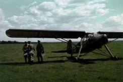 A commander departs the Fieseler Storch with two staff officers. The situation maps and papers suggest that they have just attended a situation conference.