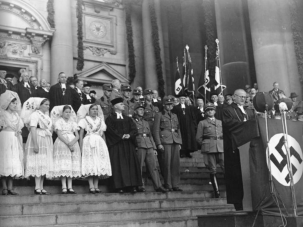 """Students salute their teacher in Berlin, January 1934. Most teachers in Nazi Germany were required to join the National Socialist Teachers League, which mandated that they take an oath of loyalty and obedience to Hitler. If their lessons did not conform to party ideals, they risked being reported by their students or colleagues. Wikimedia Commons 2 of 34 Children buy a frozen dessert from a street vendor in Berlin, 1934. Wikimedia Commons 3 of 34 Volunteers gather Christmas donations for the poor in Berlin, December 1935. Wikimedia Commons 4 of 34 Children wave flags before leaving Berlin, circa 1940-1945. These children are being evacuated from the city to live in Kinderlandverschickung camps, where they will be safe from air raids. Many will be separated from their families. Wikimedia Commons 5 of 34 Young women belonging to the League of German Girls, the female division of the Hitler Youth, practice gymnastics, 1941. Wikimedia Commons 6 of 34 German children learn geography in a Nazi-run school in the Silesia region of Poland, October 1940. Schools received a new curriculum that focused on racial biology and population policy. Teachers regularly showed propaganda films in the classroom, and worked racial politics into every part of education. Wikimedia Commons 7 of 34 Hitler Youth boys play tug of war while wearing gas masks in Worms, 1933. Wikimedia Commons 8 of 34 People at a resettlement camp in Lublin, Poland receive framed photos of Adolf Hitler to hang in their apartments, 1940. Wikimedia Commons 9 of 34 Hitler Youth members camp out in a tent at an unspecified location, 1933. Wikimedia Commons 10 of 34 A group of men read a propaganda billboard titled """"The Jews Are Our Misfortune"""" in Worms, 1933. Wikimedia Commons 11 of 34 Members of the Reich Labor Service at work, circa 1940. This state-run labor program both helped lessen the effects of unemployment and create a Nazi-indoctrinated workforce, requiring each young man to serve for a six-month period. Wik"""
