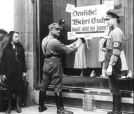 Nazi party members post signs on a Jewish storefront encouraging Germans to boycott the shop in Berlin on April 1, 1933.
