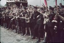 Excited crowds and Hitler Youth greet a saluting and marching German Fuhrer Adolf Hitler at Fallersleben Volkswagen Works cornerstone ceremony.