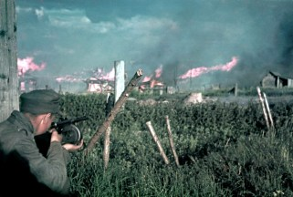Not having learned from the failed attacks during the winter of 1941-42, the Soviets again attempted to strike at the Finnish lines during the summer of 1942. This image shows the street-to-street fighting and burning of houses in Poventsa on 2 July 1942. The Finnish soldier is armed with Suomi KP/-31 submachine gun.