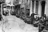 Captured German paratroopers under British guard.