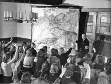 German children learn geography in a Nazi-run school in the Silesia region of Poland, October 1940. Schools received a new curriculum that focused on racial biology and population policy. Teachers regularly showed propaganda films in the classroom, and worked racial politics into every part of education.