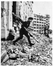 A Luftwaffe soldier, armed with a Panzerfaust 60, makes his way among debris. Berlin, late April 1945.
