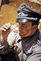 Luftwaffe officer with the rank of Oberleutnant playing cards in the North African desert with cigarette in his mouth.