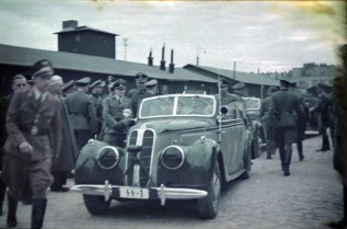 "An official visit of Heinrich Himmler in the Łódź Ghetto, Thursday, 5 June 1941. The grey-haired man is Mordechai Chaim Rumkowski. He was the ""leader"" of the Jewish community in the Lodz Ghetto (Litzmannstadt). There were a number of manufacturing enterprises in the ghetto. The German Wehrmacht had orders filled for uniform pieces and other things made by Jewish laborers. Himmler paid a brief visit to the ghetto in connection with the production taking place there. Visible also Himmler's Chief Adjudant Karl Wolff; the man with his face peeking over the shoulder of the Political officer at the far left of the frame is Ghetto Administrator, Hans Biebow; and the man next to the driver could be Dr. Wilhelm Albert."