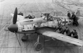 "Luftwaffe ground-crew (""black men"") positioning a Bf 109 G-6 ""Kanonenvogel"" equipped with the Rüstsatz VI underwing gondola cannon kit. Note the slats on the leading edge of the port wing. JG 2, France, late 1943."
