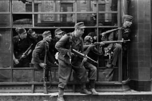 Members of the SS-Sonderregiment Dirlewanger in Warsaw in window of townhouse at Focha 9 Street. In the glass reflection one can see details of the townhouse on the opposite side of the street at Focha 8 Street August 1944.