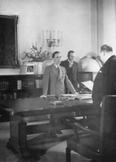 Reichsminister Goebbels has a meeting with his Staatssekretär, Walther Funk, in his office at the Ministry. In the background, Referent des Ministers Karl Hanke takes a call.