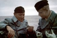 Kriegsberichter Oberleutnant Gerhard Garms (right) in U-404's conning tower, speaking with a member of the crew.
