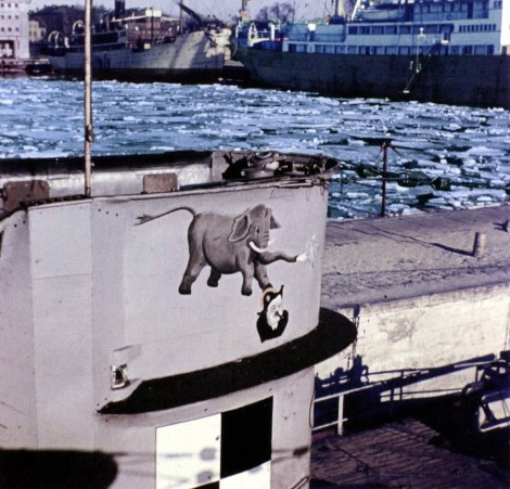 """It is U-34, wearing the emblem consisting of an elephant stepping the head of Winston Churchill, England's First Sea Lord. Beneath it is the training boat emblem. Exactly when the elephant emblem was introduced is not clear, for the boat is believed to have worn the """"Raben Huckebein"""" (Raven Huckebein) emblem during its seven operational patrols."""