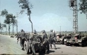German troops pulling a 37mm anti-tank gun along a road near Dunkirk. Immobilised British Scout carriers are parked at the side of the road.