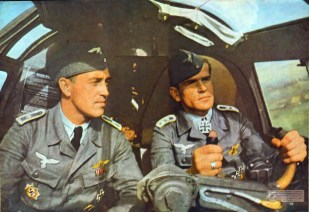 "Oberfeldwebel Johann-Peter Oekenpöhler (right) with his co-pilot. The original caption from SIGNAL magazine: ""wei Frontbewährte dt. Feldwebel probieren ein neues Modell aus. Bald sind sie wieder an der Front und noch besser für den Feind gerüstet"" (Two front sergeant try a new model for approval. Soon they are back on the front and even better equipped for the enemy)."