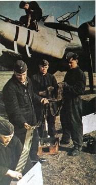 Luftwaffe armourers loading Machine-gun belts into the drums for Messerschmitt Bf 110's formidable nose armament.