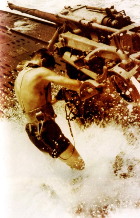 Maintenance work on the 37mm quick-firing deck gun above the U-boat in the rough sea, with the man wearing both lifejacket and safety harness.