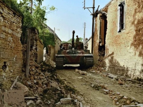 One of the three Stabskompanie Panzer VI Tigers of s.SS-Pz.Abt.102 moves through a small French village in Normandy, July 1944.