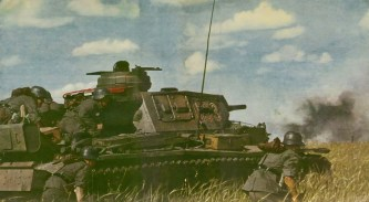 """Panzerkampfwagen III of Heeresgruppe Süd (Army Group South) advances through the Kuban Steppe on the Caucasus Mountains during Operation Blue (Unternehmen Blau/Fall Blau). The Panzer III is from the 6. Kompanie, 3. Zug and is tank number 3, going by its turret number '633'; there're a couple of symbols on the right rear mudgard- the one on the right might be that of the 1. Panzer-Division. Original caption from Signal magazine: """"tank 633 spots a Russian anti-tank emplacement and at once opens fire""""."""