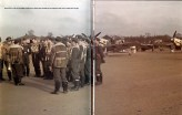 Pilots of I-JG 3 Udet at pre-flight meeting on the Channel front. Bf 109s in the background with yellow cowlings and wing tips