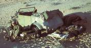 Somewhere in the North African desert soldier places on his boots near his Kübelwagen.