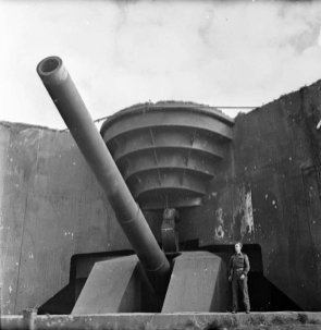 A British soldier poses next to the recently captured German 380mm gun Todt Battery at Cap Gris Nez.
