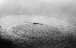 """U-459, a Type XIV supply submarine (known as a """"milch cow"""") sinking after being attacked by a Vickers Wellington."""