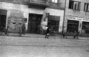"""Bunker and gate of Abschnittwache Nord (so called Nordwache) building at Żelazna 75a street behind barbed wire obstacles """"Cheval de fries"""" July 1944."""