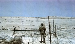 German Afrikakorps guard on duty behind barbed wire overlooking a flat desert. He is wearing short pants, tropical uniform and pith helmet with goggles. Photo taken by General Erwin Rommel during his Campaign in North Africa, 1941.