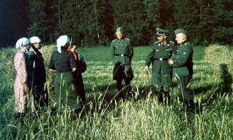 This picture was taken by Walter Frentz and it showing Reichsführer-SS Heinrich Himmler and his entourage with local peasants whilst touring the operation zones of the Einsatzgruppen, Belorussia, 15 August 1941. In the center is SS-Hauptsturmführer Werner Grothmann (Chefadjutant von Reichsführer SS Heinrich Himmler), while at right is the translator (because Himmler and Grothmann did not speak Russian).
