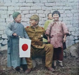 Propaganda photo of a Japanese soldier smiling to a Chinese boy holding a Japanese flag, North China 1938.