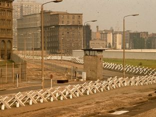 """This section of the Wall's """"death strip"""" featured Czech hedgehogs, a guard tower and a cleared area, 1977."""
