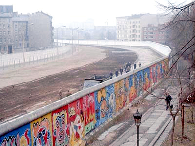 """View from the West Berlin side of graffiti art on the wall in 1986. The wall's """"death strip"""", on the east side of the wall, here follows the curve of the Luisenstadt Canal (filled in 1932)."""