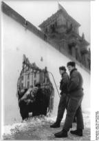 West Germans peer at East German border guards through a hole in the wall. 5 January 1990.