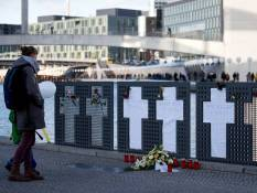 A passersby looks at commemorative crosses for those who died at the Berlin Wall along the Spree River with the Border of Light balloons in the background.