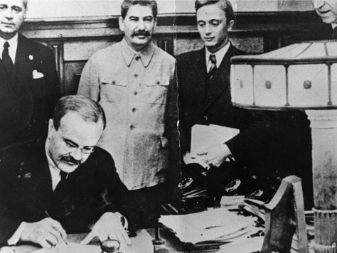 Molotov signs the non-aggression pact in the presence of Ribbentrop (left) and Stalin (centre left).