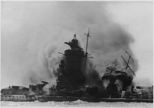 The Admiral Graf Spee is on fire and begins to sink.