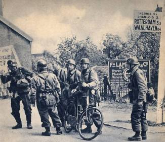 Five Fallschirmjägers and one airlanding soldier discuss the events unfolding in the early morning of the the 10th May on a road-crossing near Waalhaven AFB. The bike is most likely commandered from a Dutch civilian.