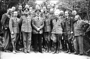 Hitler with his staff at his Wolf's Lair field headquarters in May or June 1940. Heinrich Hoffmann is in the front row on the far right