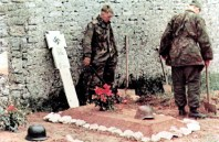 """Men of SS-Panzergrenadier-Regiment 25 / 12.SS-Panzer-Division """"Hitlerjugend"""" erect temporary grave crosses for SS-Oberscharfuhrer Helmut Belke along the walls of Abbaye d'Ardenne (Ardenne Abbey) during the first days of the Normandy Invasion."""
